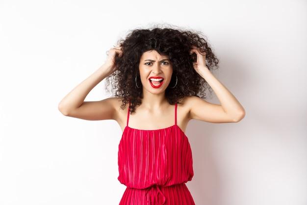 Sfrustrowana kręcona kobieta w czerwonej sukience, marszcząca brwi i krzycząca wściekła, wyrywająca włosy i krzycząca do kamery, stojąca na białym tle.