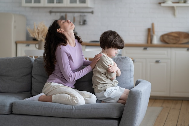 Sfrustrowana matka zmęczona upartym synem obrażony i zdenerwowany próbuje pocieszyć małego chłopca ignorując mamę