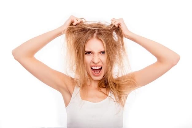 Sfrustrowana młoda blondynka trzymająca swoje zniszczone włosy i wrzeszcząca