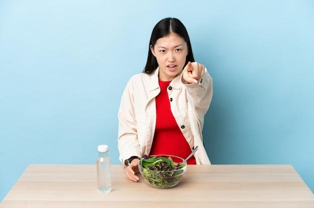 Sfrustrowana młoda chinka je sałatkę i wskazuje na przód