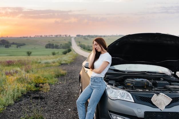 Sfrustrowana młoda dziewczyna stoi obok zepsutego samochodu na środku autostrady podczas zachodu słońca. awaria i naprawa samochodu. czekam na pomoc.