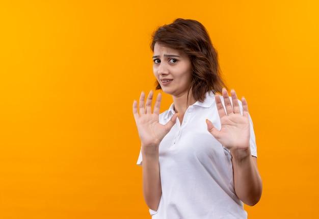 Sfrustrowana młoda dziewczyna z krótkimi włosami na sobie białą koszulkę polo, czyniąc gest obrony z obrzydzonym wyrazem
