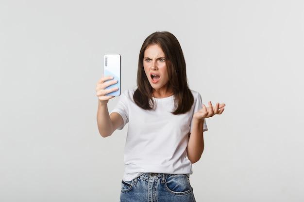 Sfrustrowana młoda kobieta kłóci się przy rozmowie wideo, trzymając smartfon, stojąc na biało.