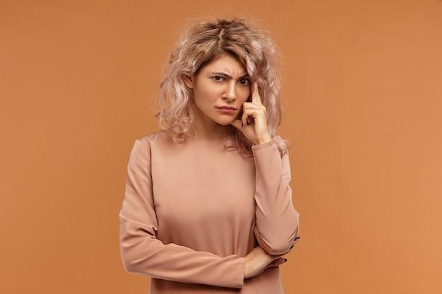 Sfrustrowana młoda kobieta o różowawych włosach i zestresowanym wyglądzie