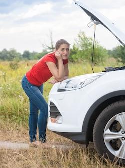 Sfrustrowana młoda kobieta patrząca na zepsuty silnik samochodu na wiejskiej drodze