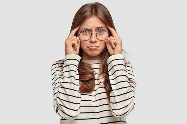 Sfrustrowana młoda kobieta w okularach pozuje przy białej ścianie