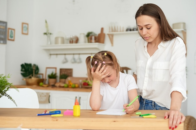 Sfrustrowana młoda matka lub nauczyciel uczący dziecko w domu zdalnej edukacji szkolnej
