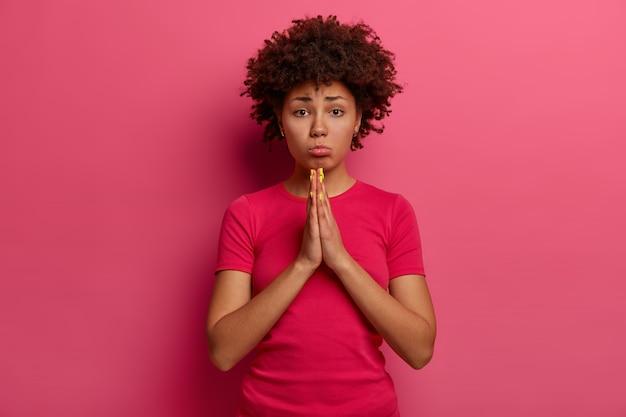 Sfrustrowana, nieszczęśliwa kobieta z kręconymi włosami błaga o pozwolenie