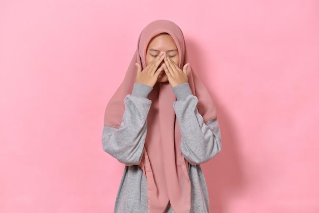 Sfrustrowana, nieszczęśliwa, zmęczona młoda muzułmanka robi minę dłonią, ma zamknięte oczy i wzdycha ze zmęczenia, nosi hidżab, pozuje na różowym tle, denerwuje, ma dosyć