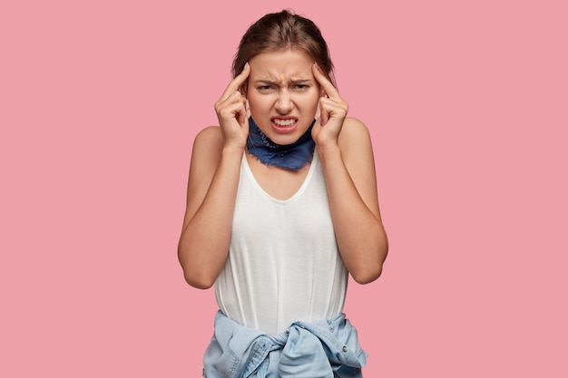 Sfrustrowana piękna kobieta trzyma palce wskazujące na skroniach, cierpi na migrenę