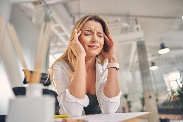 Sfrustrowana pracownica cierpiąca na migrenę siedząc przy stole w biurze