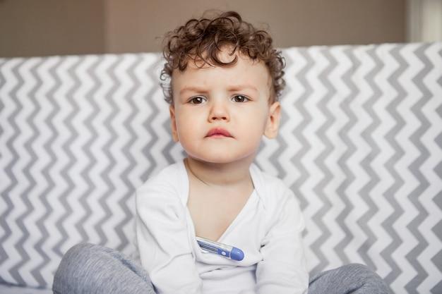 Sfrustrowane dziecko mierzy temperaturę. chore dziecko