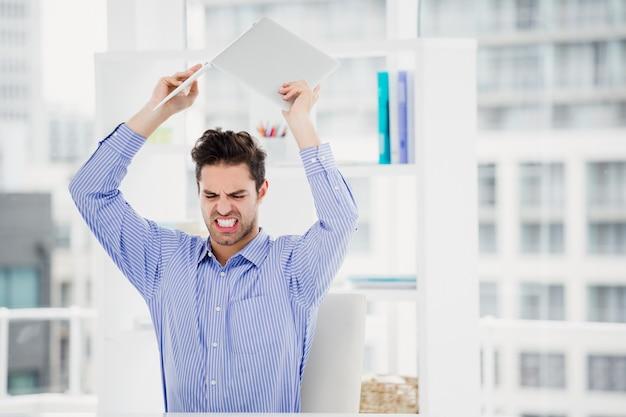 Sfrustrowany biznesmen rzuca laptopa