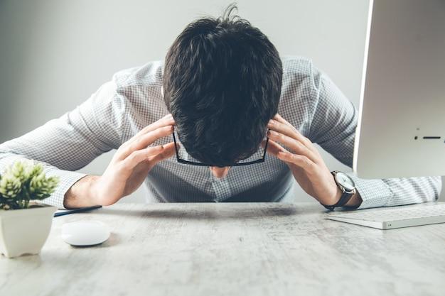 Sfrustrowany biznesmen siedzi na biurku z ręką na głowie w biurze