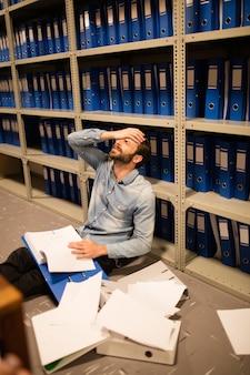 Sfrustrowany biznesmen z teczką i dokumentami siedzi w magazynie