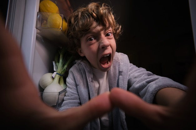 Sfrustrowany chłopiec przy otwartej lodówce z jedzeniem