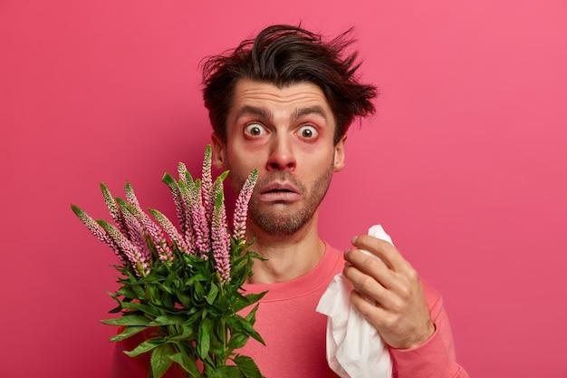 Sfrustrowany chory kicha z powodu uczulenia na pyłki, trzyma chusteczkę i przeciera nos, jest uczulony na wiosenne kwiaty, ma opuchnięte oczy, wymaga leczenia, wdmuchuje chusteczkę. choroba sezonowa