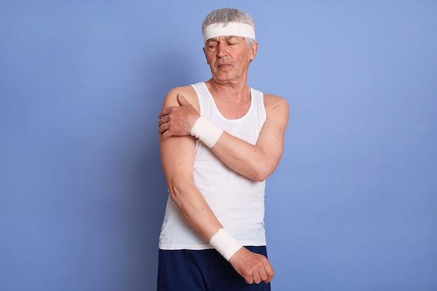 Sfrustrowany dziadek emeryta z silnym bólem karku, ubrany w białą koszulkę bez rękawów, opaskę na włosy i pasek w talii pozuje na białym tle.