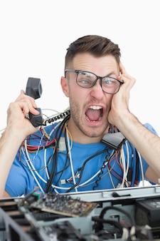 Sfrustrowany informatyk krzyczy na telefon przed otwartym cpu