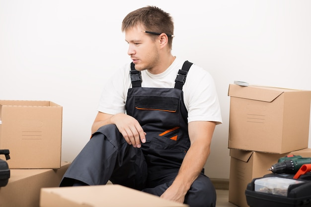 Sfrustrowany mężczyzna siedzący między brązowymi kartonami po przeprowadzce, nie wiedząc, co robić. zrób to sam, nowa koncepcja domu i przeprowadzki
