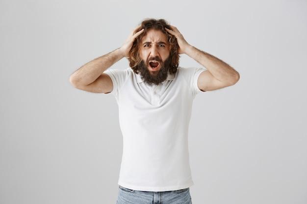 Sfrustrowany mężczyzna wyglądający na rozczarowanego z rękami na głowie