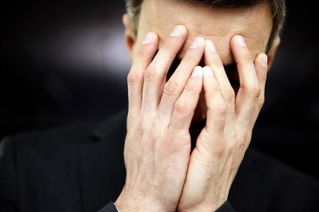 Sfrustrowany mężczyzna z rękami na twarzy