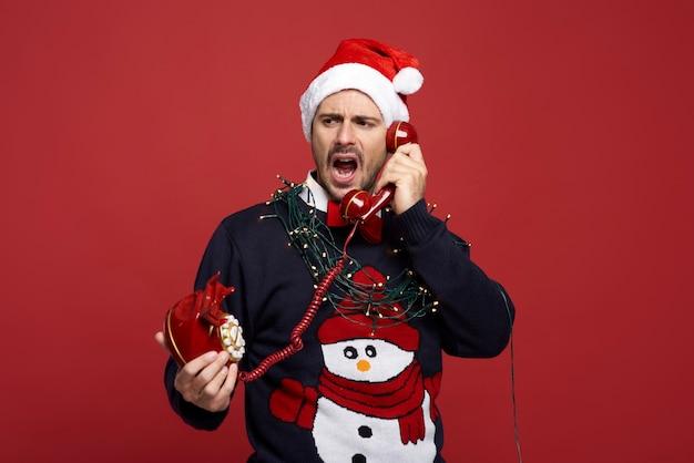 Sfrustrowany mężczyzna z telefonem stacjonarnym