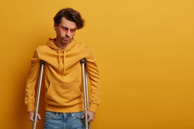 Sfrustrowany mężczyzna z zranioną twarzą ponownie uczy się chodzić, stojąc o kulach