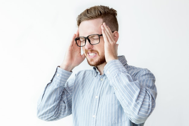 Sfrustrowany młody biznesmen dotykając ból głowy