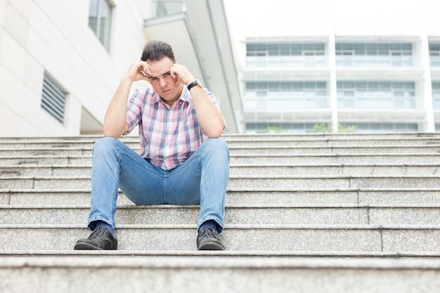 Sfrustrowany młody człowiek siedzi na city stairway