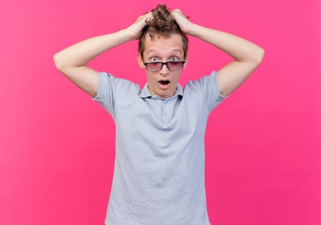 Sfrustrowany młody człowiek w czarnych okularach, ubrany w szarą koszulkę polo, dotykający głowy, ciągnąc za włosy, stojąc na różowej ścianie