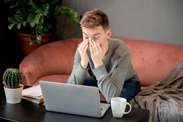 Sfrustrowany młody człowiek wygląda na wyczerpanego i zasłania twarz rękami, siedząc przy laptopie w swoim domowym miejscu pracy