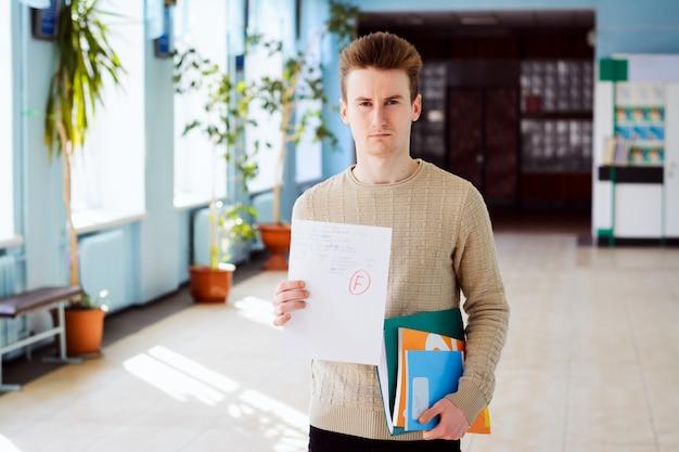 Sfrustrowany młody student ze złym wynikiem testu pokazując papier do aparatu