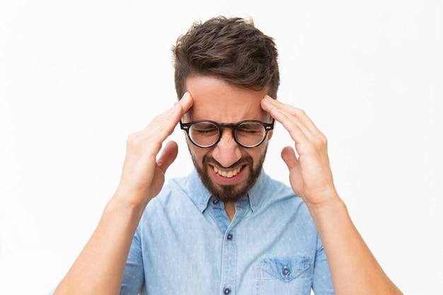 Sfrustrowany nieszczęśliwy facet dotyka głowy z grymasem bólu