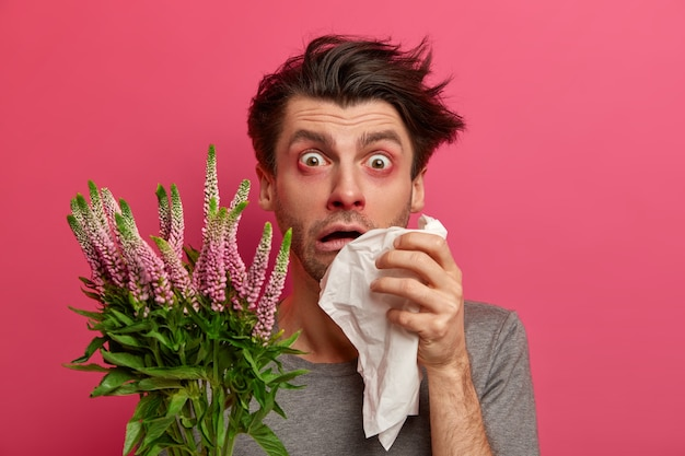 Sfrustrowany niezdrowy mężczyzna cierpi na alergię, łzawią oczy, ma katar, trzyma chusteczkę i patrzy z rozpaczą, wrażliwy na sezonowe alergeny ma duszność