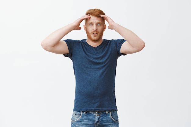 Sfrustrowany ponury rudy mężczyzna w niebieskiej koszulce, trzymający głowę i wpatrzony w rozczarowanie, przegrywający zakład, odczuwający dewestację i żal, stojący nad szarą ścianą nieszczęśliwy