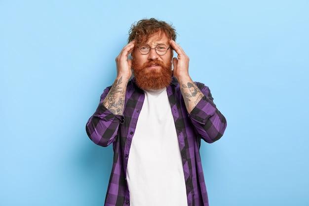 Sfrustrowany rudowłosy mężczyzna z gęstą brodą dotyka skroni, cierpi na ogromną migrenę, potrzebuje środków przeciwbólowych