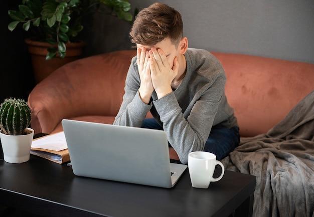 Sfrustrowany student młody człowiek szuka wyczerpany i zasłania twarz rękami, siedząc przy laptopie w swoim domowym miejscu pracy