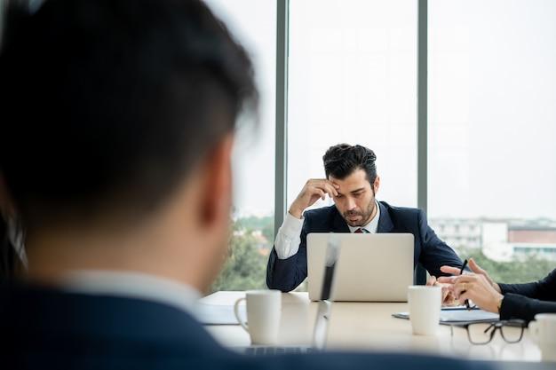 Sfrustrowany szef przygnębiony niepowodzeniem firmy złe wieści z grupą biznesmenów w sali konferencyjnej