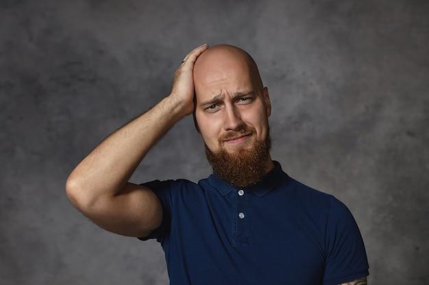 Sfrustrowany, żałosny, stylowy młody mężczyzna z gęstą brodą o zapominającej zdziwieniu miny, dotykający ogolonej głowy, próbujący coś sobie przypomnieć. brodaty facet cierpiący na straszny ból głowy