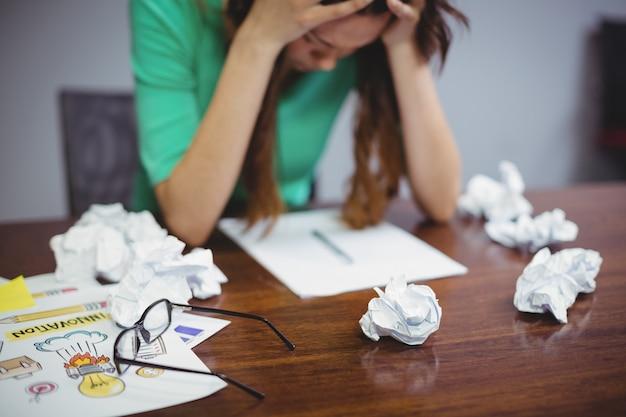 Sfrustrowany żeński dyrektor wykonawczy siedzi z piłkami pogniecionych papierów