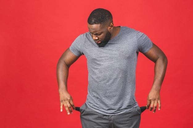 Sfrustrowany zmartwiony murzyn, afroamerykanin, pokazujący puste kieszenie, pokazujący, że nie mam pieniędzy, jest bankrutem