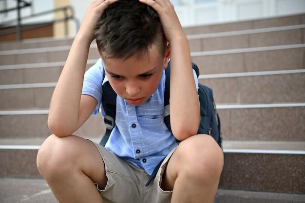 Sfrustrowany zmartwiony uczeń trzymający się za głowę rękami, siedząc na schodach w pobliżu szkoły. pojęcie trudności w nauce, zastraszania, samotności