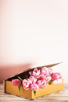 Shabby chic dekoracja - różowe tulipany w starej książce z miejscem na kopię