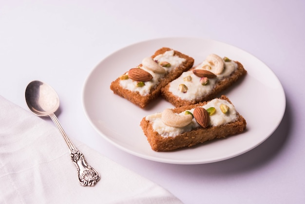 Shahi tukda lub double ka meetha to budyń chlebowy w ghee, udekorowany skondensowanym mlekiem, orzechami i mawą/khoya. popularny indyjski deser, podawany w talerzu na nastrojowym tle. selektywne skupienie