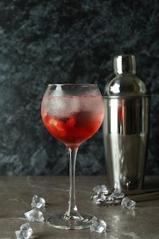 Shaker i szklanka świeżego letniego koktajlu na szarym stole