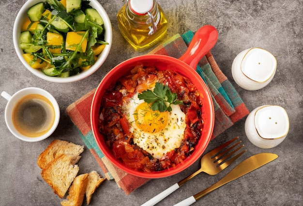 Shakshuka w czerwonej patelni na szarym tle, śniadaniowym pojęciu z smażonym jajkiem, sałatką i kawą