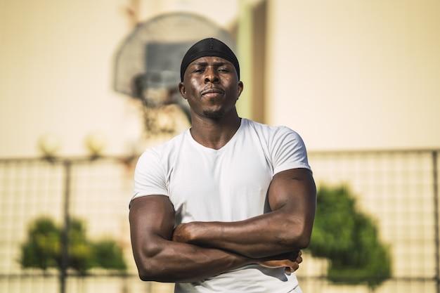 Shallow focus shot of african-american mężczyzna w białej koszuli stwarzających z rękami skrzyżowanymi