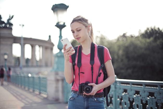 Shallow focus strzał młodej kobiety robi wycieczkę po mieście i trzymając w rękach smartfon