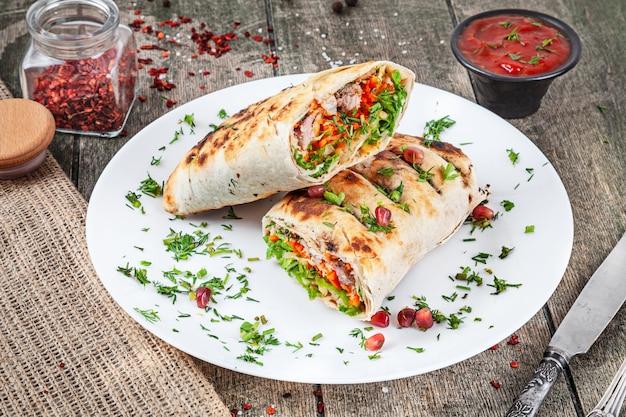 Shaurma, shawerma, kebab podawane na białym talerzu z sosem. wegańskie jedzenie z falafelem. kuchnia arabska lub wschodnia. kopiowanie miejsca, selektywne fokus. shaurma z przyprawami, pomidorkami cherry i papryką